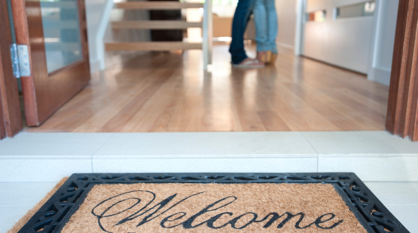 Happy young couple standing inside their new house with a welcome mat at the front door