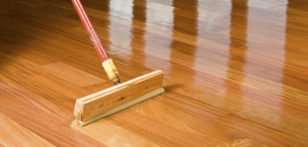 Squeegee Style Brush Applying Clear Polyurethane to Hardwood Flo
