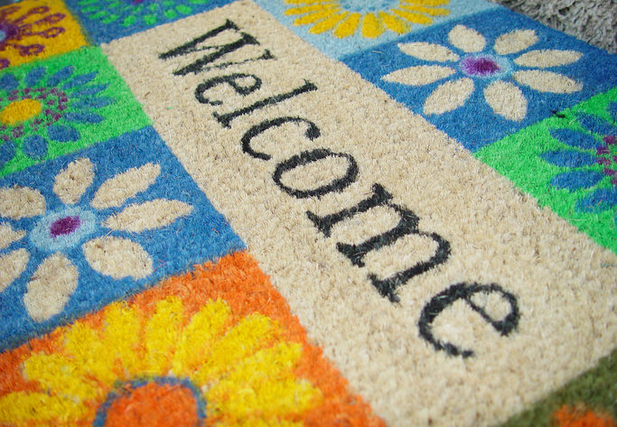 Sideview of a colorful doormat decorated with flowers. On the doormat the word welcome can be read in diagonal.